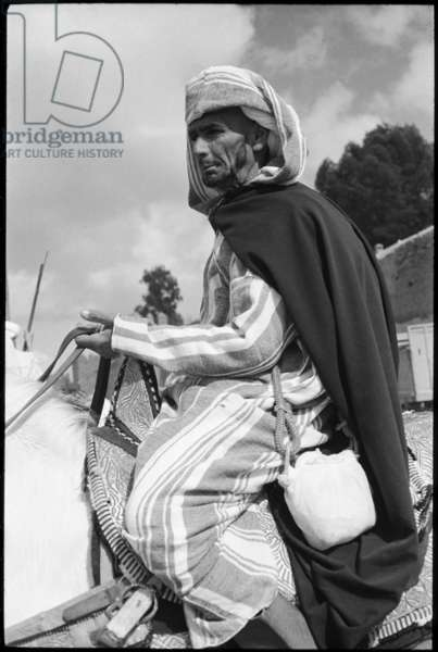 Portrait of a man, sitting astride a horse, awaiting the arrival of King Hassan II during the Feast of the Throne, Marrakesh, Morocco, 1965 (b/w photo)