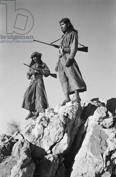 Portrait of Salim bin Ghabaisha and Salim bin Kabina, two of Wilfred Thesiger's Bedouin companions, standing on a rock outcrop in Ras Al Khaimah Emirate, United Arab Emirates, March – April 1950 (b/w photo)