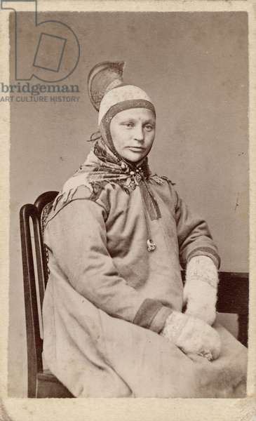 A half–length portrait of a seated woman wearing traditional Saami dress. She is dressed in a tunic, mittens, is wearing a hat with a high crest, and a triangular scarf tied around her neck. She also has a pendant hanging possibly from the cord that ties her hat under her chin, c.1870s (albumen print)