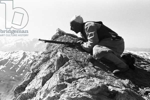 View of a man, crouching on rocks, hunting bear in the mountains above Rust, Iraq, May – September 1951 (b/w photo)