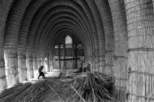 Interior view of the unfinished mudhif (guest house) belonging to Raudha, with bundles of reeds lying on the ground, Rumaila, Iraq, 1955 (b/w photo)