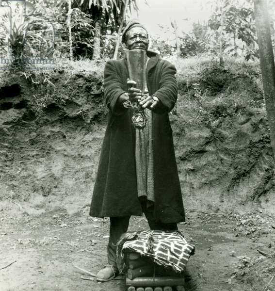 Mfaomi Baa with a 'Ngwelem' War Gong, 1958 (gelatin silver print)