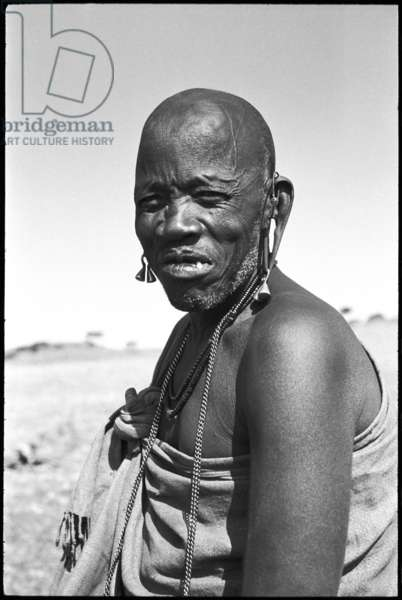 Portrait of an elderly man, a Maasai elder, wearing metal earrings and a necklace, Ngorongoro District, Tanzania, 1963 (b/w photo)