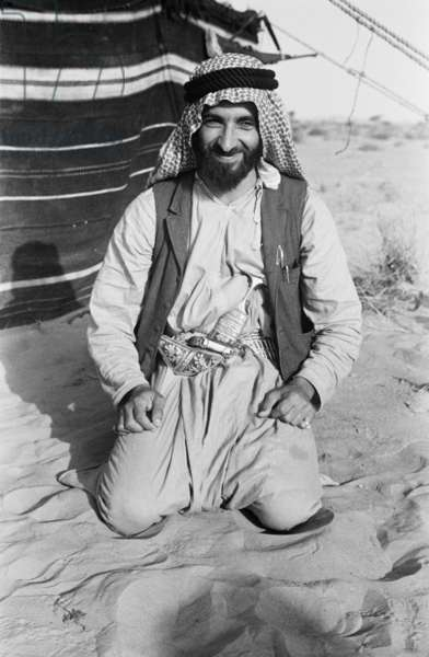 Seated portrait of Sheikh Zayed bin Sultan Al Nahyan in front of a tent at his hunting camp near Al Ain, United Arab Emirates, April 6-30, 1948 (b/w photo)