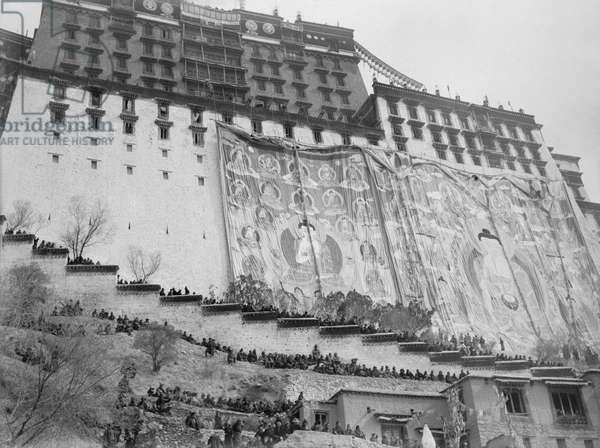 The south face of the Potala hung with two silk applique banners of the Buddha surrounded by other Buddhas and Bodhisattvas, Lhasa, Tibet, 1946-50 (b/w photo)