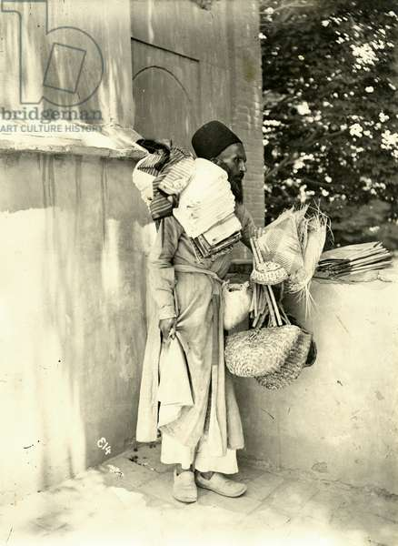 A portrait of a street seller, holding baskets and cloth over his shoulder, Iran, c.1900 (gelatin silver print)