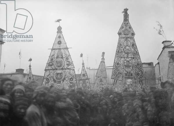 Large chopa votive offerings being paraded through a crowd as part of the ceremonies of the 'Offerings of the Fifteenth', 22nd February 1921 (glass plate gelatin print)