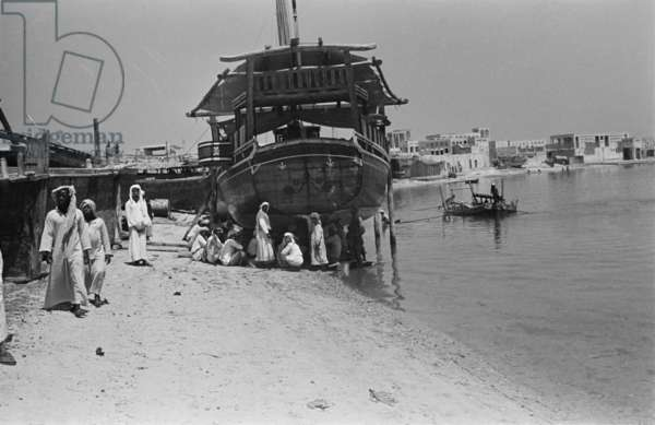 View of locals sitting alongside a dhow (sailboat) beached on the shore at Dubai Creek, Dubai, United Arab Emirates, April 9-24, 1949 (b/w photo)