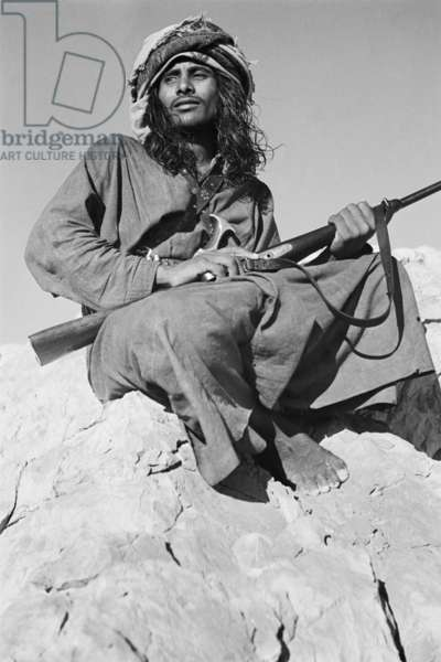 Seated portrait of Salim bin Ghabaisha, one of Wilfred Thesiger's Bedouin companions, in Ras Al Khaimah Emirate, United Arab Emirates, March – April 1950 (b/w photo)