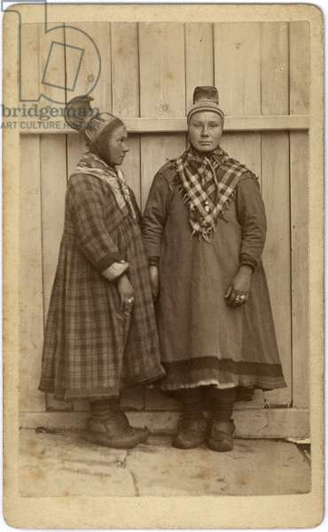 Two women standing side by side, both wearing 'traditional' Saami dress.  One is posed frontally, the other in profile, c.1870s (albumen print)