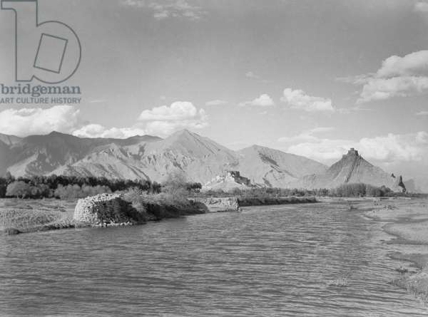 A view of the Kyichu River with the Potala and Chakpori visible in the distance, taken from the north, Lhasa, Tibet, 1936-37 (b/w photo)