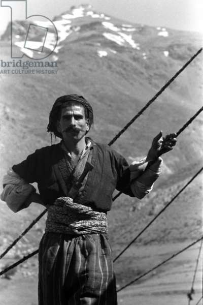 Portrait of a man, standing, leaning on some ropes, Gunda Zhor, Iraq, May – September 1951 (b/w photo)