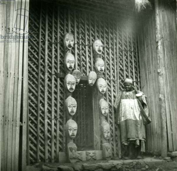Fai Kitukelae, head of the major Nso lineage, in front of his meeting house. Door surrounded with 'mbot' wooden carved heads, 1958 (gelatin silver print)