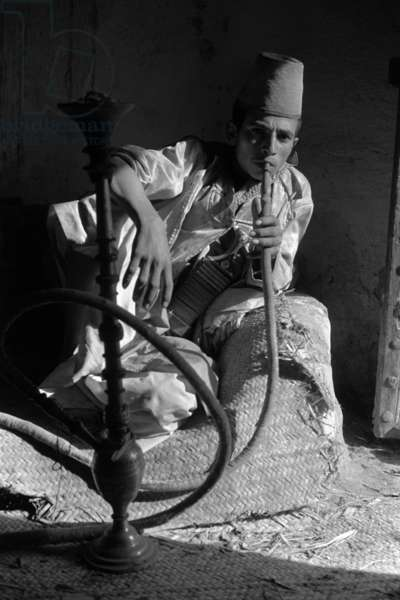 Portrait of a young man, sitting on a chair, wearing a plaited conical hat, smoking a water-pipe, Shahra, Yemen, June – November 1966 (b/w photo)