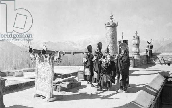 Four Gelugpa monks blowing ceremonial horns on the roof of Kundeling monastery, Lhasa, Tibet, 14th February 1937 (gelatin silver print)