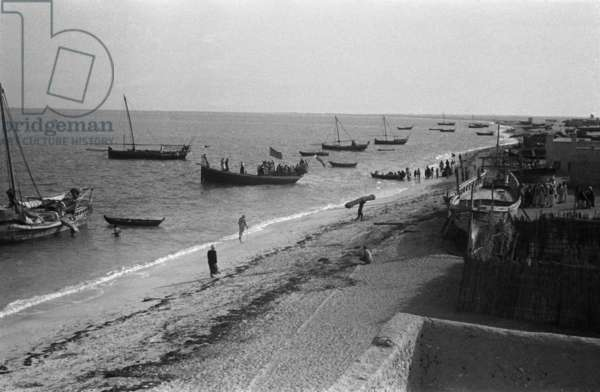View of boats moored off the Corniche in the town of Abu Dhabi, United Arab Emirates, March 14-16, 1948 (b/w photo)
