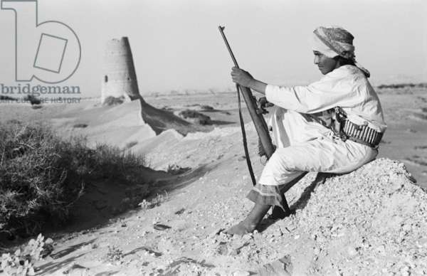 Seated profile portrait of Salim bin Ghabaisha, one of Wilfred Thesiger's Bedouin companions, near a watchtower in the Al Ain/Buraimi Oasis, United Arab Emirates, April 6-30, 1948 (b/w photo)