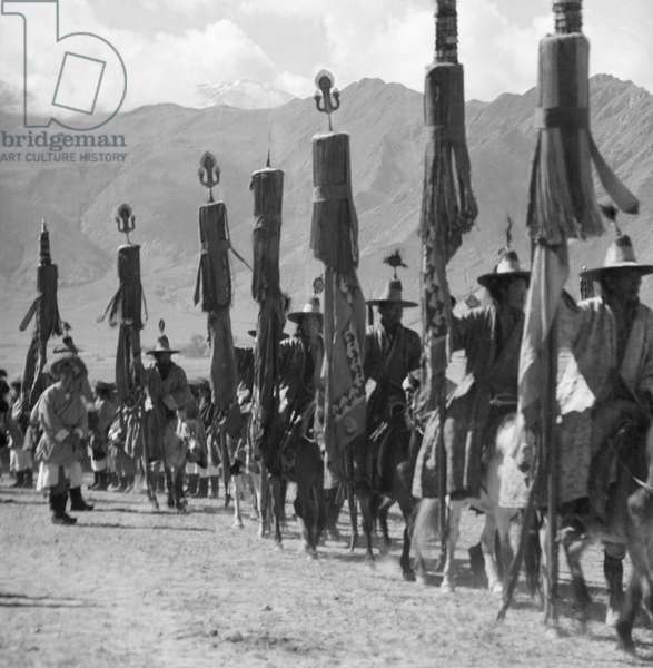 Horsemen in ceremonial dress and wearing conical hats with brims carrying banners and standards surmounted by tridents, Doguthang, Rikya, Tibet, 8th October 1939 (b/w photo)