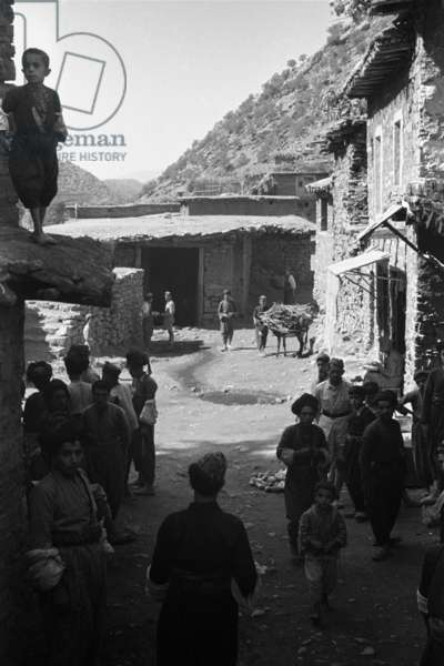 View of houses at Tawila, with people gathered on the street in the foreground, Iraq, August – October 1950 (b/w photo)