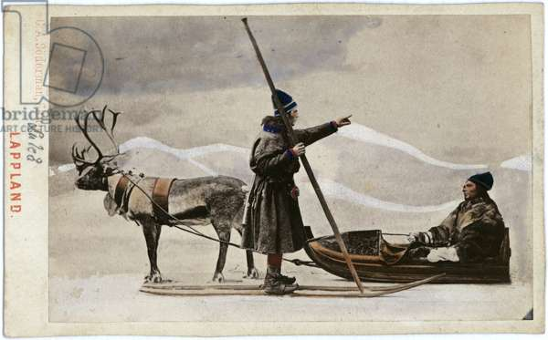 Two men in a snow covered landscape.  One is sitting low to the ground in a sledge being pulled by a reindeer.  The second, facing him pointing into the distance, wears skis and is carrying a long rod, almost twice his height, perhaps a ski or hunting/ fishing accessory, c.1870s (hand-tinted albumen print)