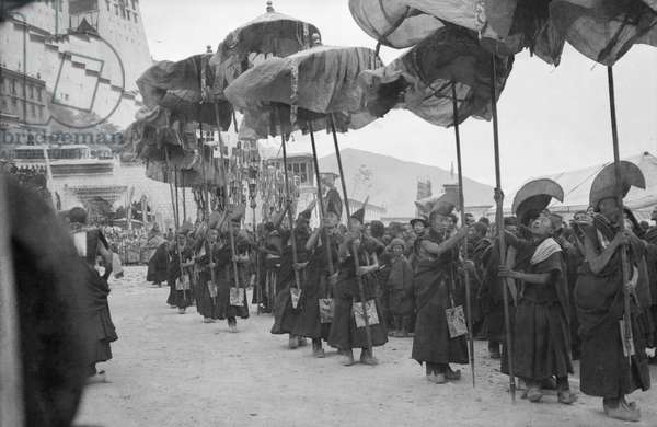 Monks carrying banners waiting in the procession below the Potala at the Sertreng festival held on the 30th day of the second Tibetan month, Lhasa, Tibet, 1949-50 (b/w photo)