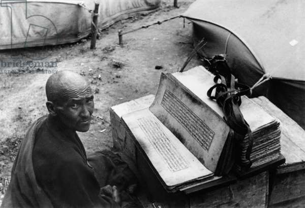 A lama doctor, or amchi, reading religious texts outside a sick man's tent, Dekyi Lingka, Lhasa, Tibet, 3rd September 1936 (gelatin silver print)