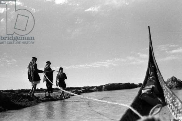 View of the prow of Wilfred Thesiger's tarada (sheikh's canoe), being towed with a rope by three young men walking at the water's edge, Iraq, 1956 (b/w photo)