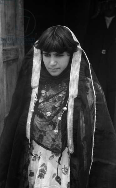 Portrait of a young woman, one of the daughters of Warid bin Shinta, standing in the doorway of a house, Al Ashima, Iraq, 1952 (b/w photo)
