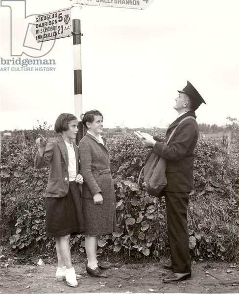 A postman consults a bilingual signpost in Belleek, Northern Ireland, 1938 (b/w photo)