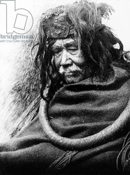 The Hamatsa, Nakoaktok c. 1910 Half-length portrait of Nakoaktok man, facing left, wearing cedar root ceremonial loop.