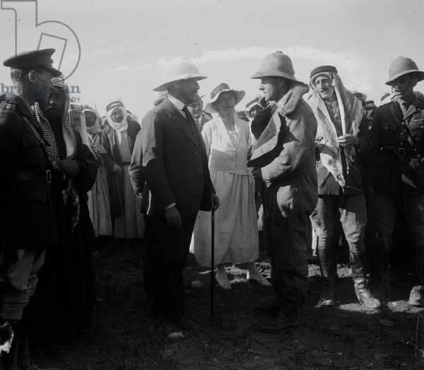 Pilot in flight suit greets Sir Herbert Samuel. Gertrude Bell, stands between Samuel and pilot. Wyndham Deedes and Amir Abdullah to the left in foreground 1921  American Colony (Jerusalem).