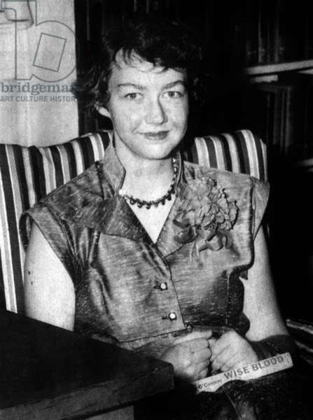 American writer Flannery O'Connor (1925-1964) with her book