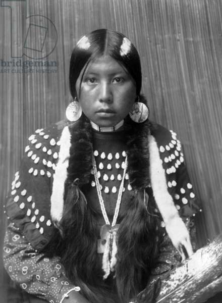 Kalispel Indian woman, white stripes painted on hair, shell disk earrings, wearing blanket dress decorated with elks' teeth, c. 1910, photo Edward S. Curtis