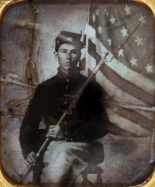 Young soldier in Union uniform with bayoneted musket in front of American flag, American Civil War (1861-1865)