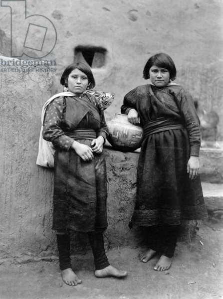 Two Zuni girls standing in front of pueblo buildings, New Mexico, c. 1903, photo Edward S. Curtis