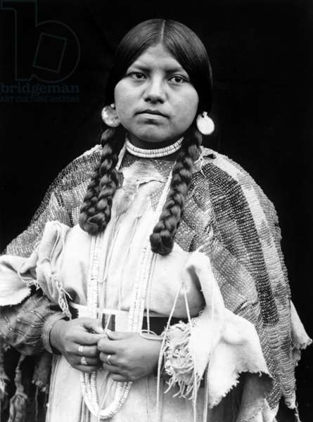 Cayuse woman, half-length portrait, standing, facing front, braids, shell disk earrings, shell bead choker and shell beads around neck, beaded buckskin dress with beaded belt c. 1910, photo Edward S. Curtis