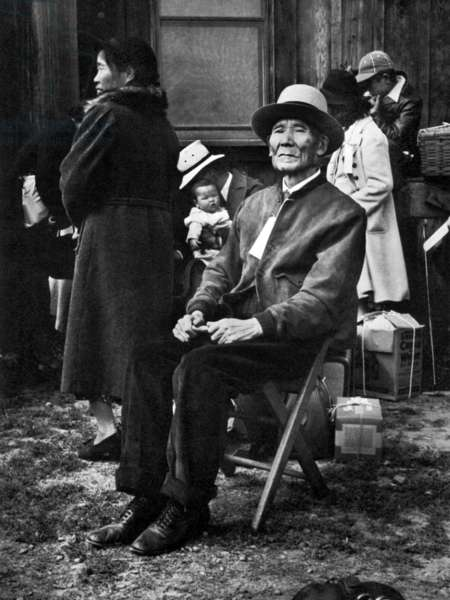 An elderly Japanese American man and a family with baby await relocation in Centerville, California. May 19th 1942 (b/w photo)
