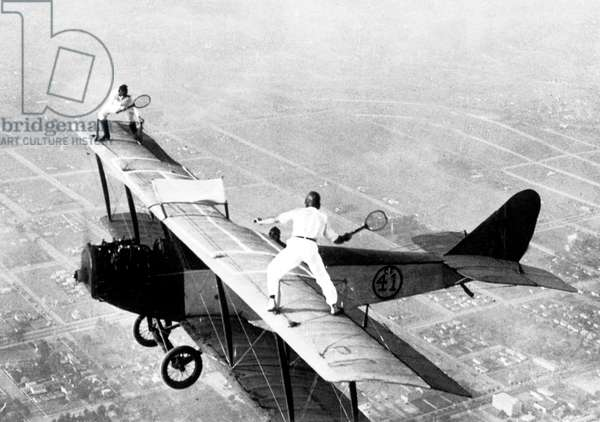 """Ivan Unger and Gladys Roy playing tennis on the roof of a flying Curtiss JN-4 """"Jenny"""" plane 1925oof of a flying plane 1925"""