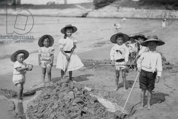 Children playing with sand on the beach, c. 1920