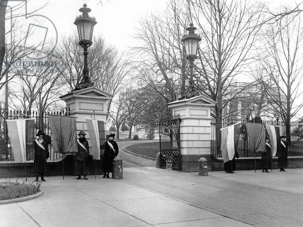 Suffragists with banners picket the White House asking for President Woodrow Wilson's support the 19th Amendment, January 1917 (b/w photo)