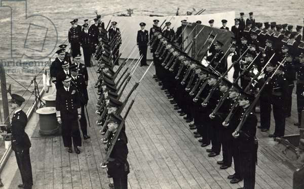 HM King George inspecting Royal Marines of the ship's Royal Marine Detachment aboard the cruiser HMS Belfast during a visit to the ship, April 1943 (b/w photo)