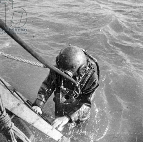 A Royal Navy diver emerging from the water, c.1900 (b/w photo)
