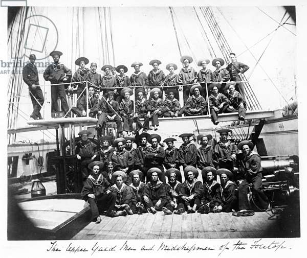 Group portrait of Upper Yard Men and Midshipmen of the Foretop from the cruiser HMS Phoebe (launched 1890), pictured on the deck of the vessel, c.1894 (b/w photo)