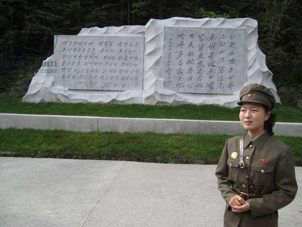 North Korean guide near plaque in Paektu Secret Camp, where Kim Jong-il is alleged to have been born, 2008 (photo)
