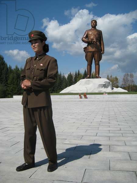 North Korean guide standing in front Statue of former Leader Kim il-Sung near Mount Paektu, which forms part of the Samjiyon Grand Monument, 2008 (photo)