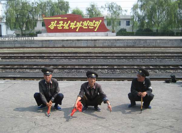 North Korean Railway Officials squatting by the side of the track, 2008 (photo)