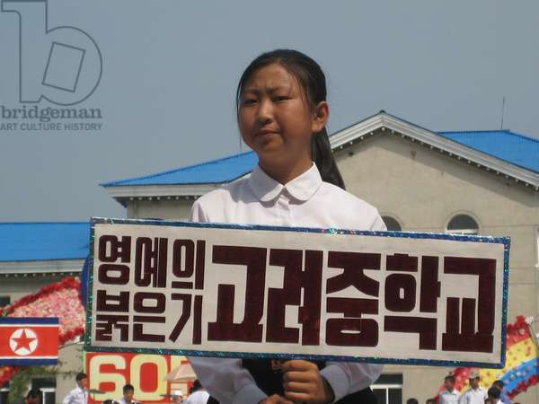 Schoolgirl holding propaganda placard at the celebrations of the 60th Anniversary of the founding of North Korea in Kaesong City, 2008 (photo)