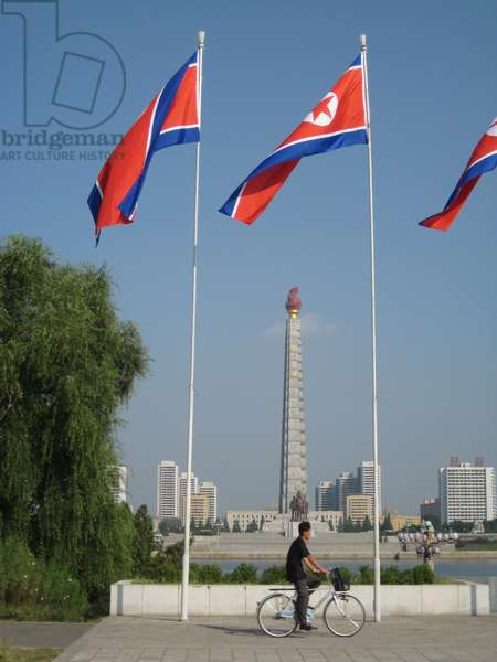 Bicyclist passing in front of North Korean flags, behind is the Juche Tower, Pyongyang, 2008 (photo)