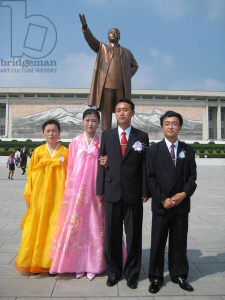 North Korean couples standing in front Statue of former Leader Kim il-Sung, known as the Mansudae Monument, Pyongyang, 2008 (photo)