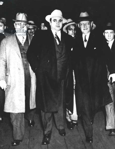 Al Capone (1899-1947) leaving Chicago, escorted by William H. Thompson and Laubenheimer, to serve his prison sentence in Atlanta, 1932 (b/w photo)